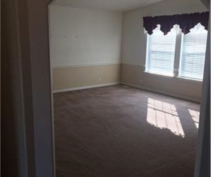 Entry into carpeted living room with large windows